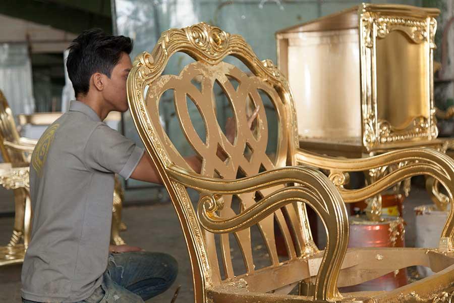 تصویر یکی از هنرمندان رنگکار مبل سلامی در حال انجام ورق طلا